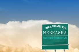 Nebraska state sign under a blue sky.