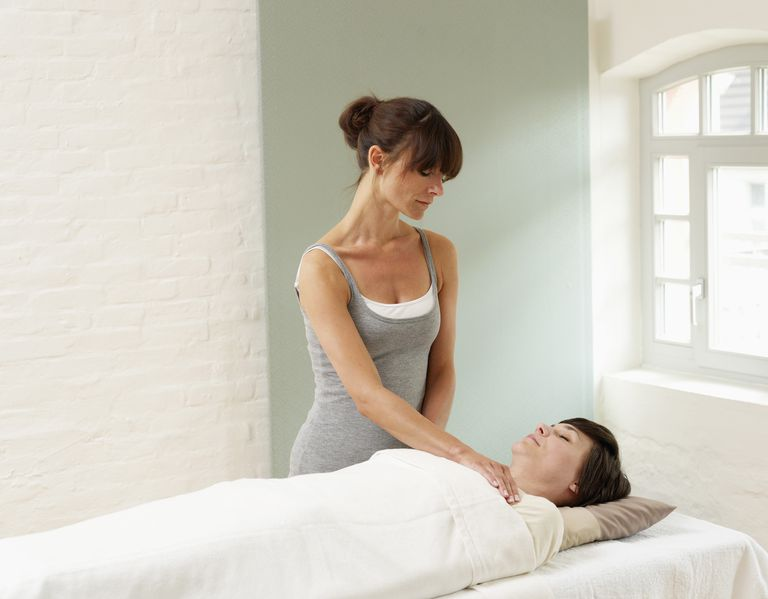 Woman receiving reiki treatment from masseur