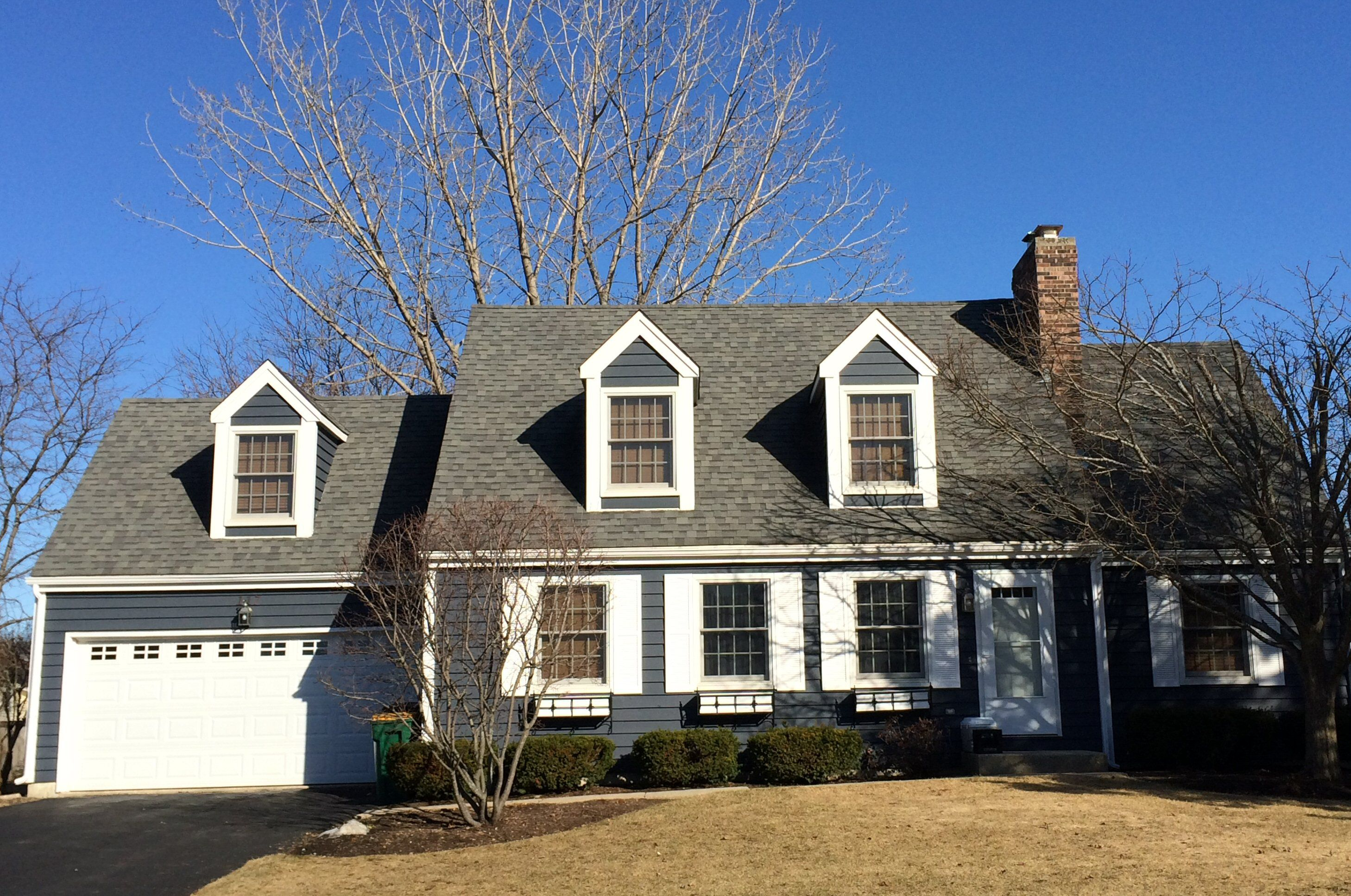 Cape cod style house with two dormers on the house and one over the garage door