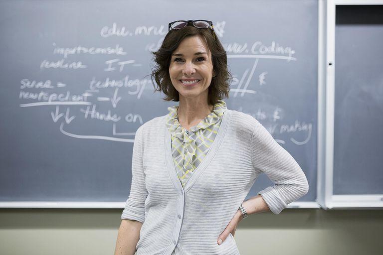 Profesora delante de pizarra.