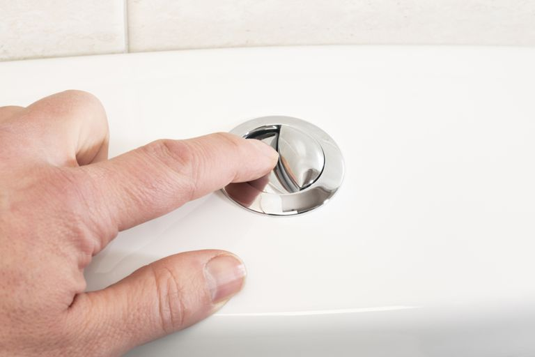 A hand pressing a button of a dual flush toilet