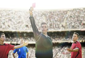 Exuding poise under trying circumstances, a referee flashes a red card in a soccer match
