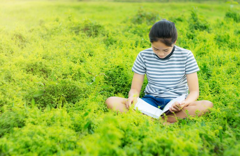 Young-teen-girl-reading-book-in-field
