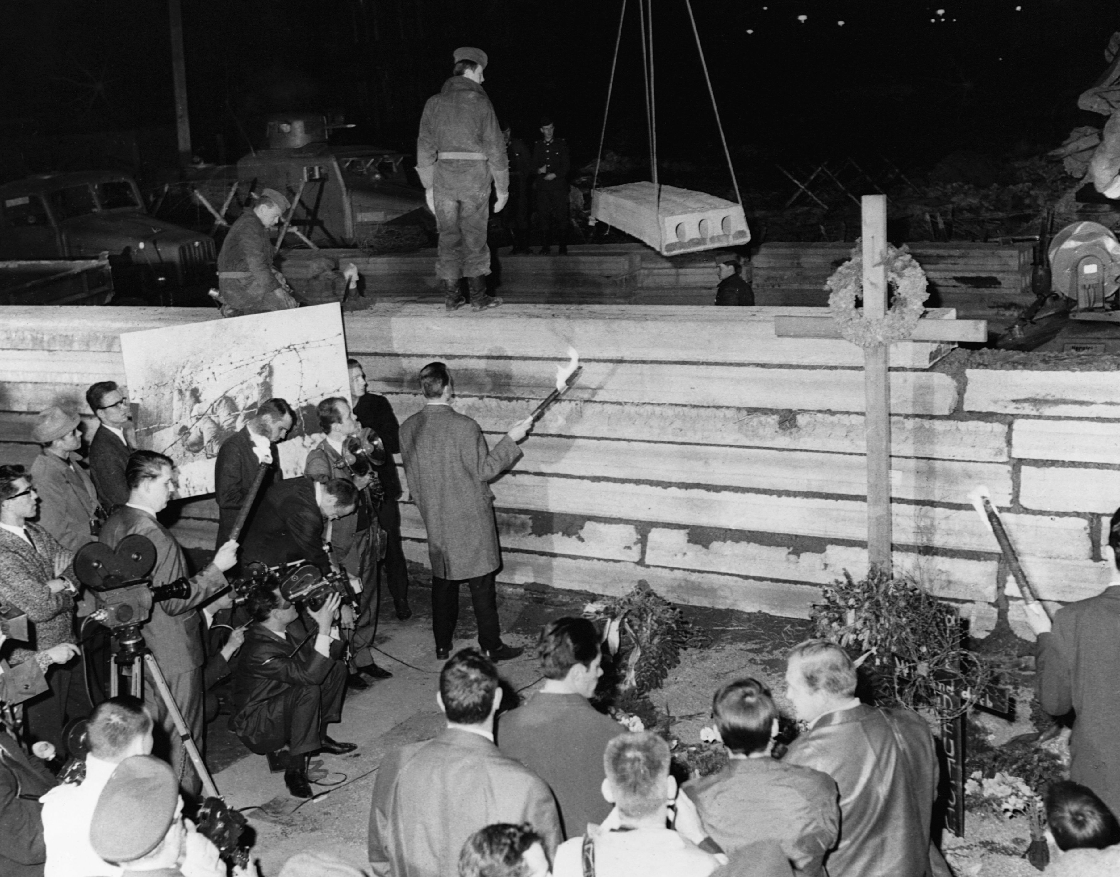 West Germans protest death of Peter Fechter as East German soldiers rebuild part of the wall.