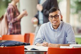 student smiling at table