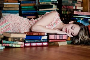 Woman sleeping with many books on floor of library