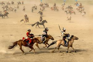 Dozens of Mongolian riders on horses racing across the sand.