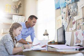 A teacher helping a teen girl study