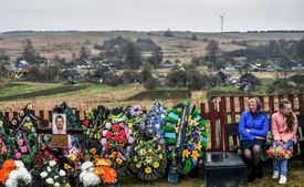 A woman and her daughter visit the grave of a relative at a cemetery in Belarus during Radunitsa day, once associated with Rod and the Rozhanitsy.