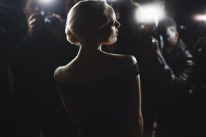 A woman haloed by the flash of photographers on a red carpet