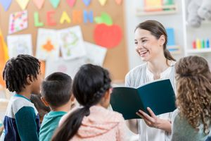 Young teacher listens to student during group story time