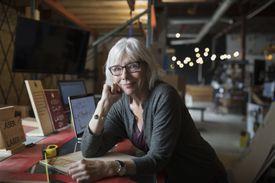 Portrait confident senior female machinist working at laser cutter in workshop