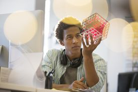 Businessman examining cube at his desk in an office