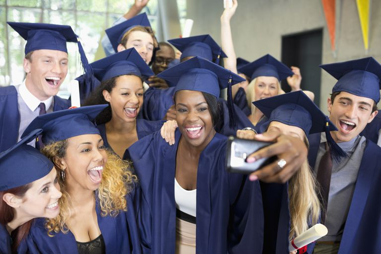Group of smiling students in graduation gowns taking selfie on graduation day