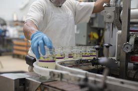 Man handling glass jars on production line