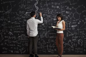 Boy and girl work together in math chalkboard