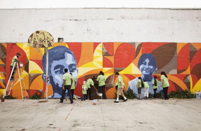 Volunteers painting a wall mural