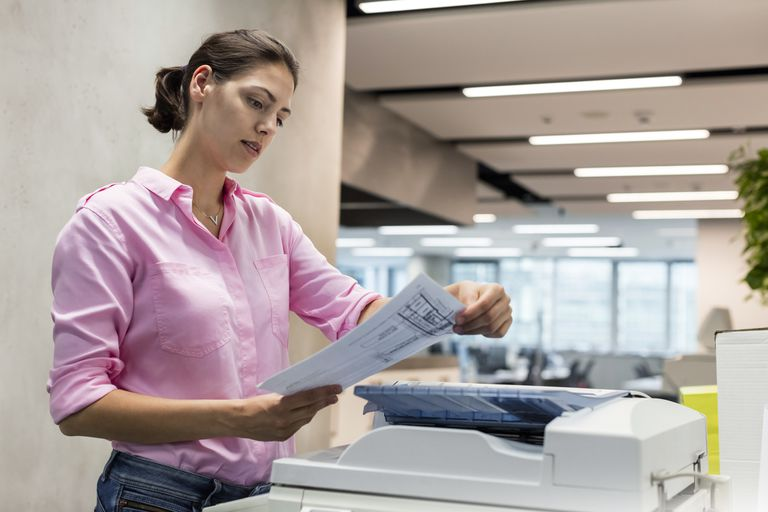 A businesswoman using an office printer