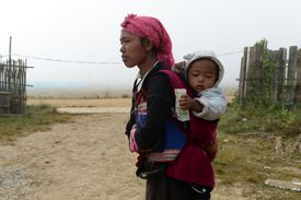 An Asian woman carries her baby on her back