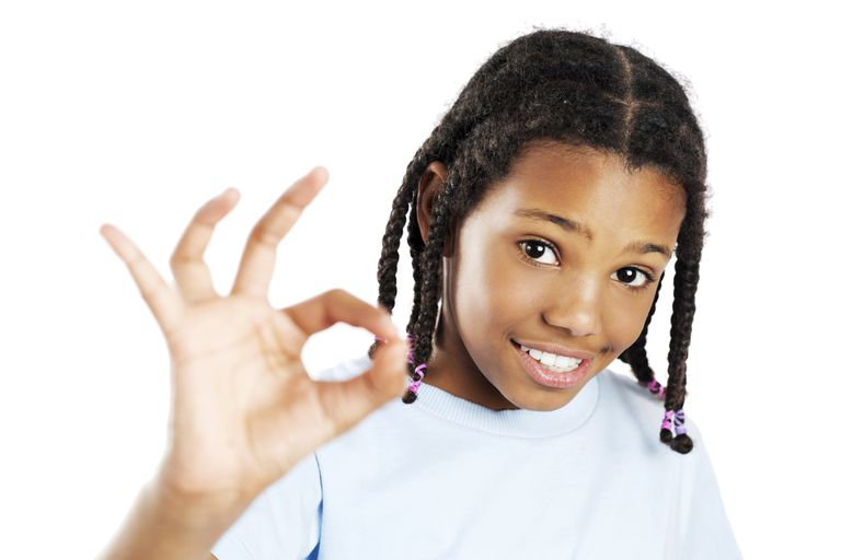 Girl smiling and holding up her hand showing the OK sign