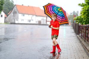 A boy plays in the rainy street with an umbrella and galoshes