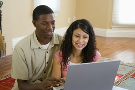 Young couple using laptop, indoors.