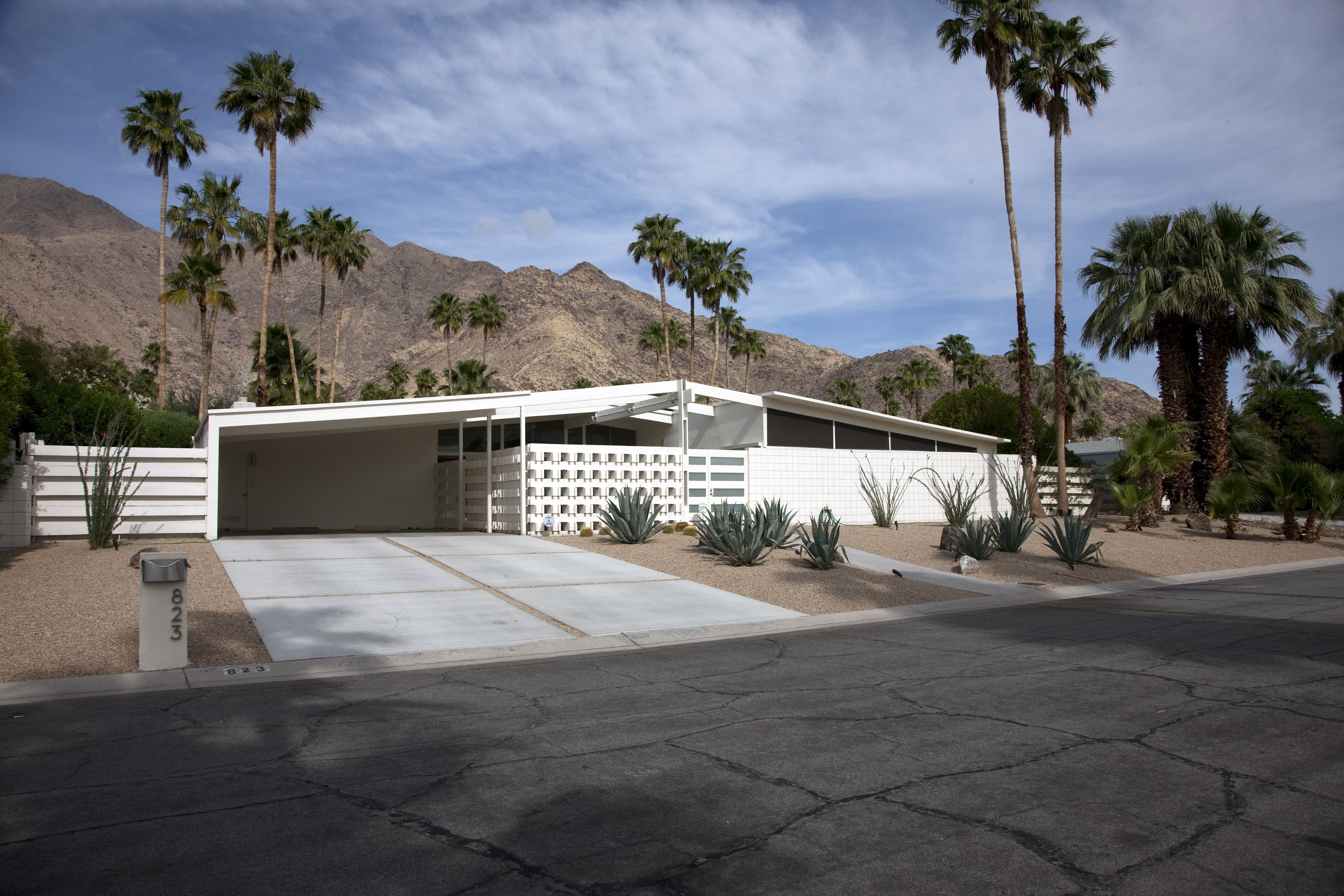 modern, horizontal-oriented white home with open carport, slanted roof, and situated beneath rocky hills