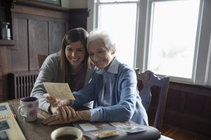 An older and younger woman look at images from scrapbook