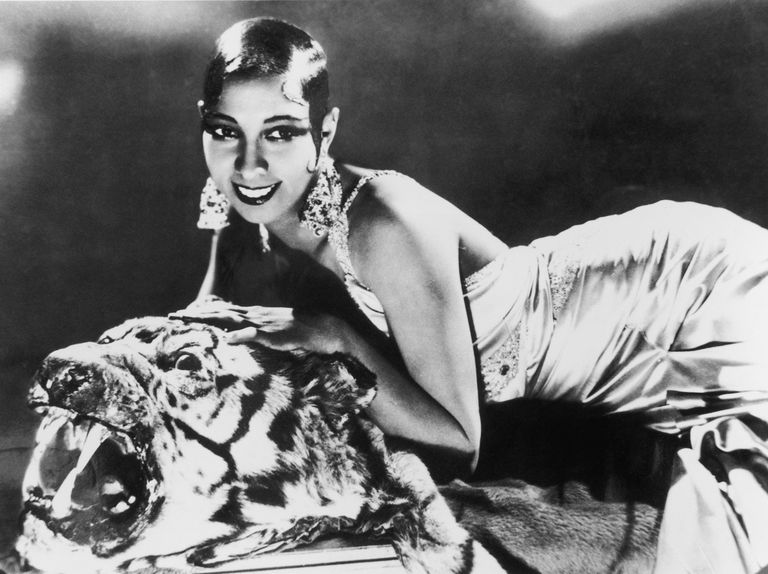 Josephine Baker on top of a tiger rug while wearing a silk gown.