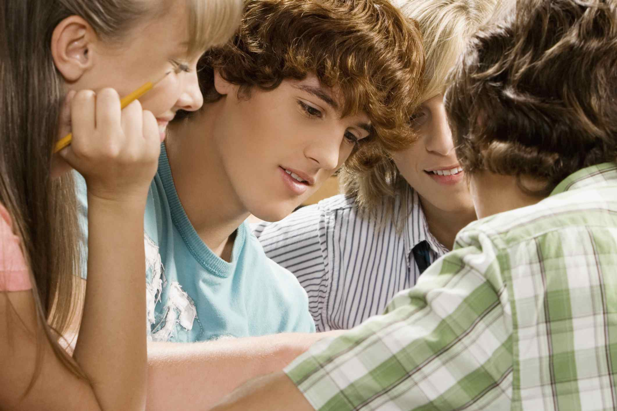 Students gathered closely together looking at classwork