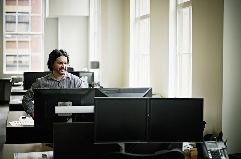 Smiling businessman in office looking at monitor