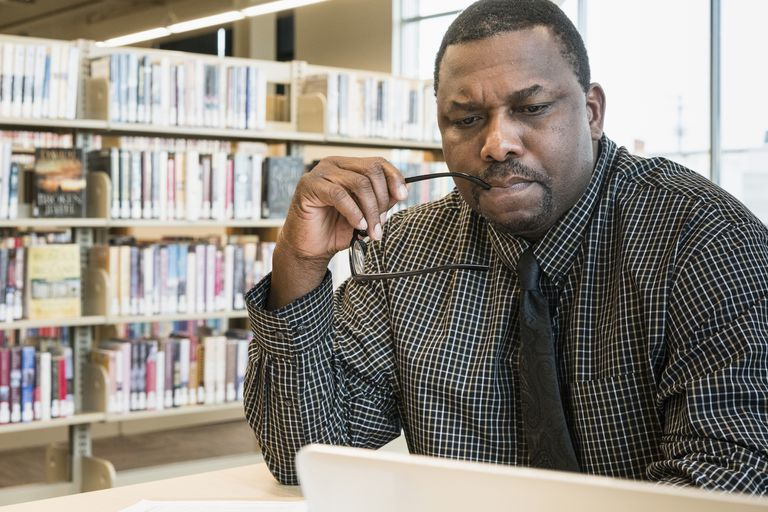 Black man using laptop in library