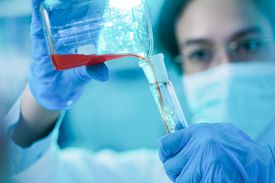 Close up of a student working on scientific experiment in laboratory.