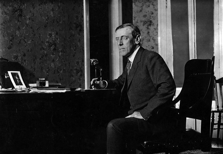 Black and white photograph of Woodrow Wilson sitting at his desk.