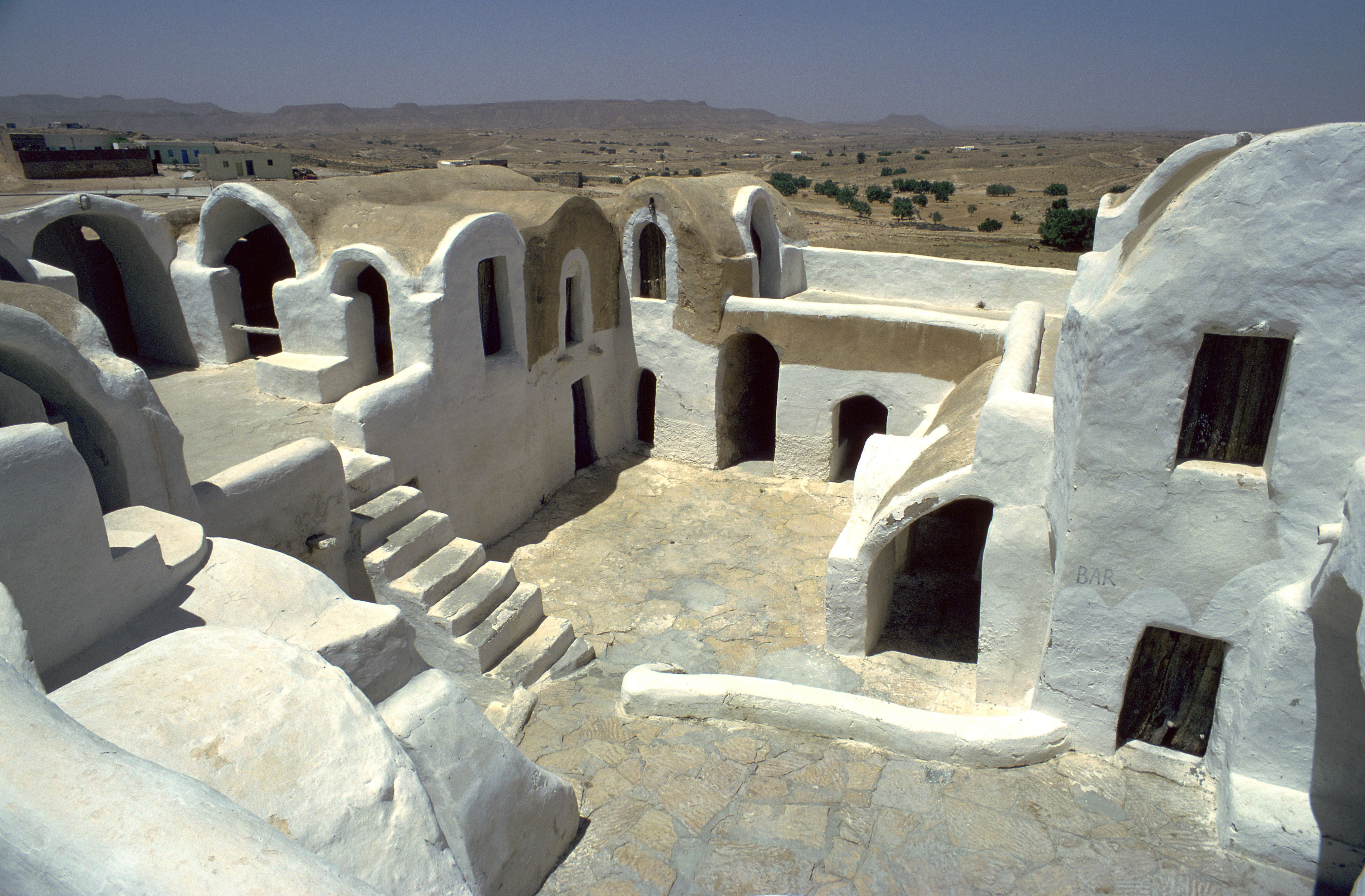 white earthen structures built beneath the earth's surface but open to the air with multiple windows, doors, and stairways