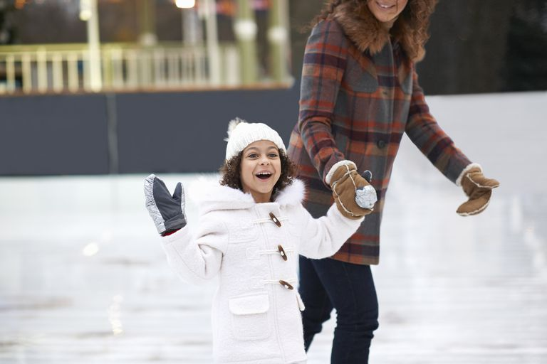 Girl ice skating with mother, holding hands looking at camera smiling