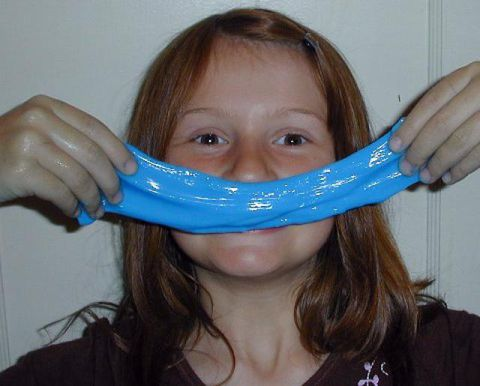 girl holding up blue slime