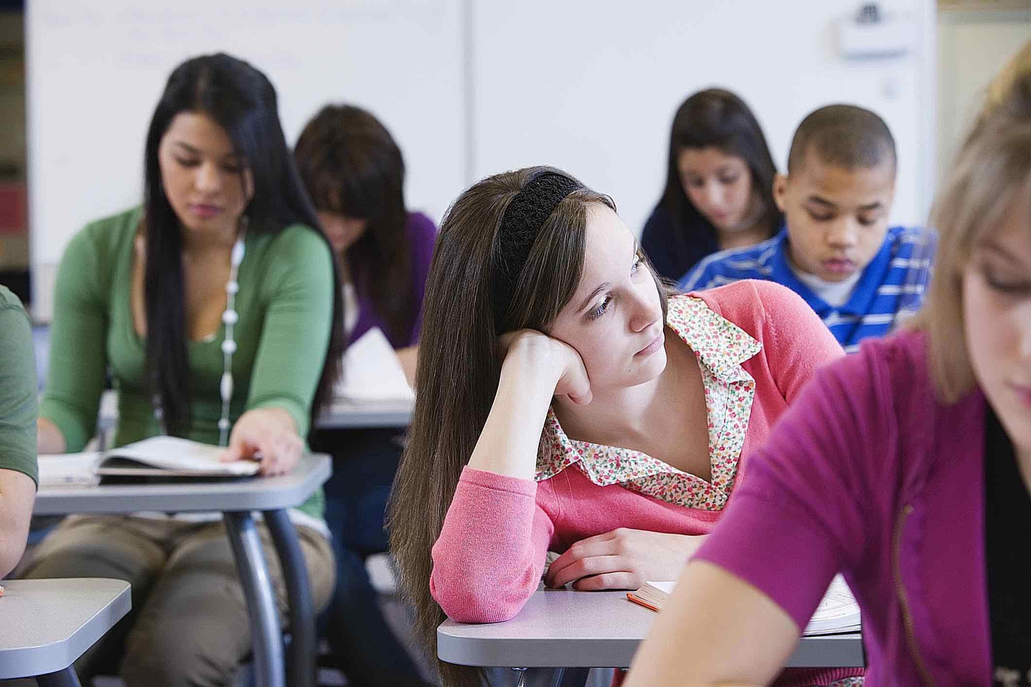 Teenage girl (16-17) sitting in classroom, looking away