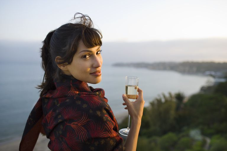 Woman holding champagne glass, ocean in background