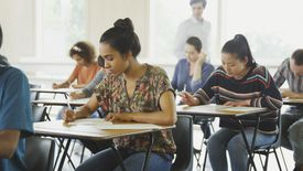 College students taking test at desks in classroom.