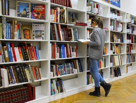 Young woman browsing the shelves at a library.