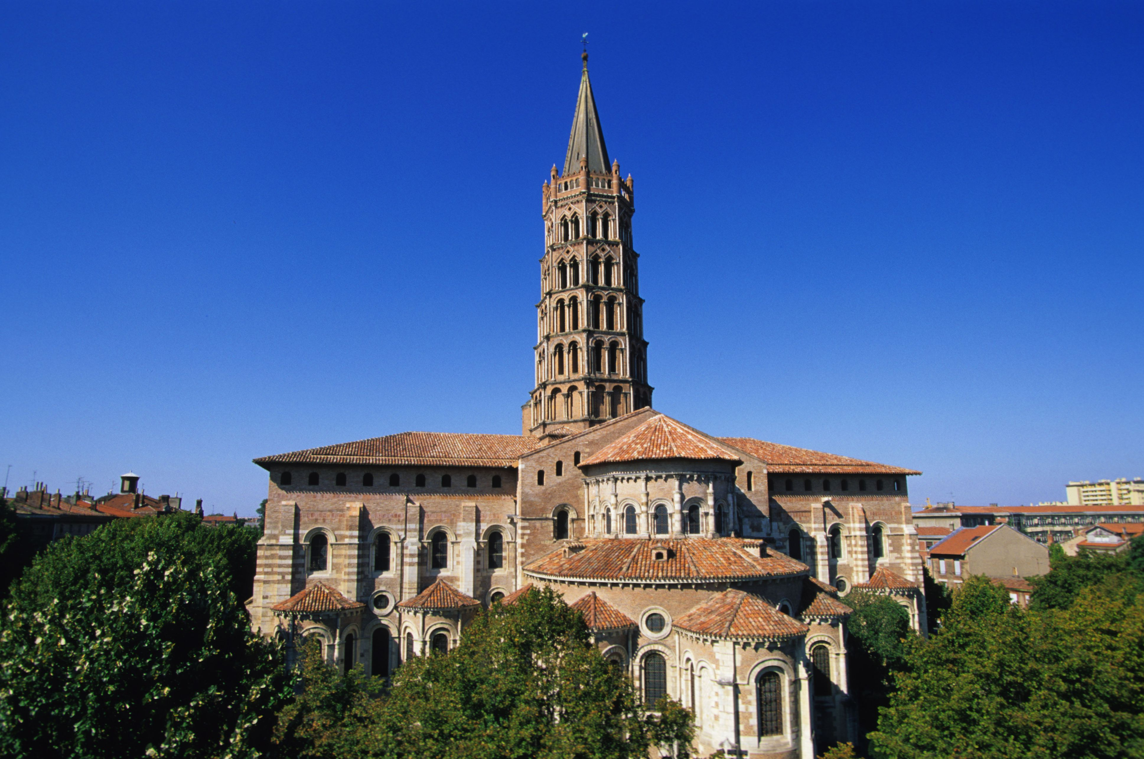 Rounded arches, massive walls, tower of the Basilica of St. Sernin (1070-1120) in Toulouse, France