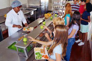 Woman serving food to schoolchildren in cafeteria.
