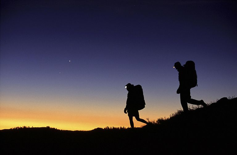 two hikers with headlamps at night
