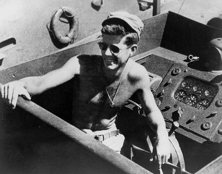 John F. Kennedy, shirtless and wearing sunglasses while at the helm of PT-109.