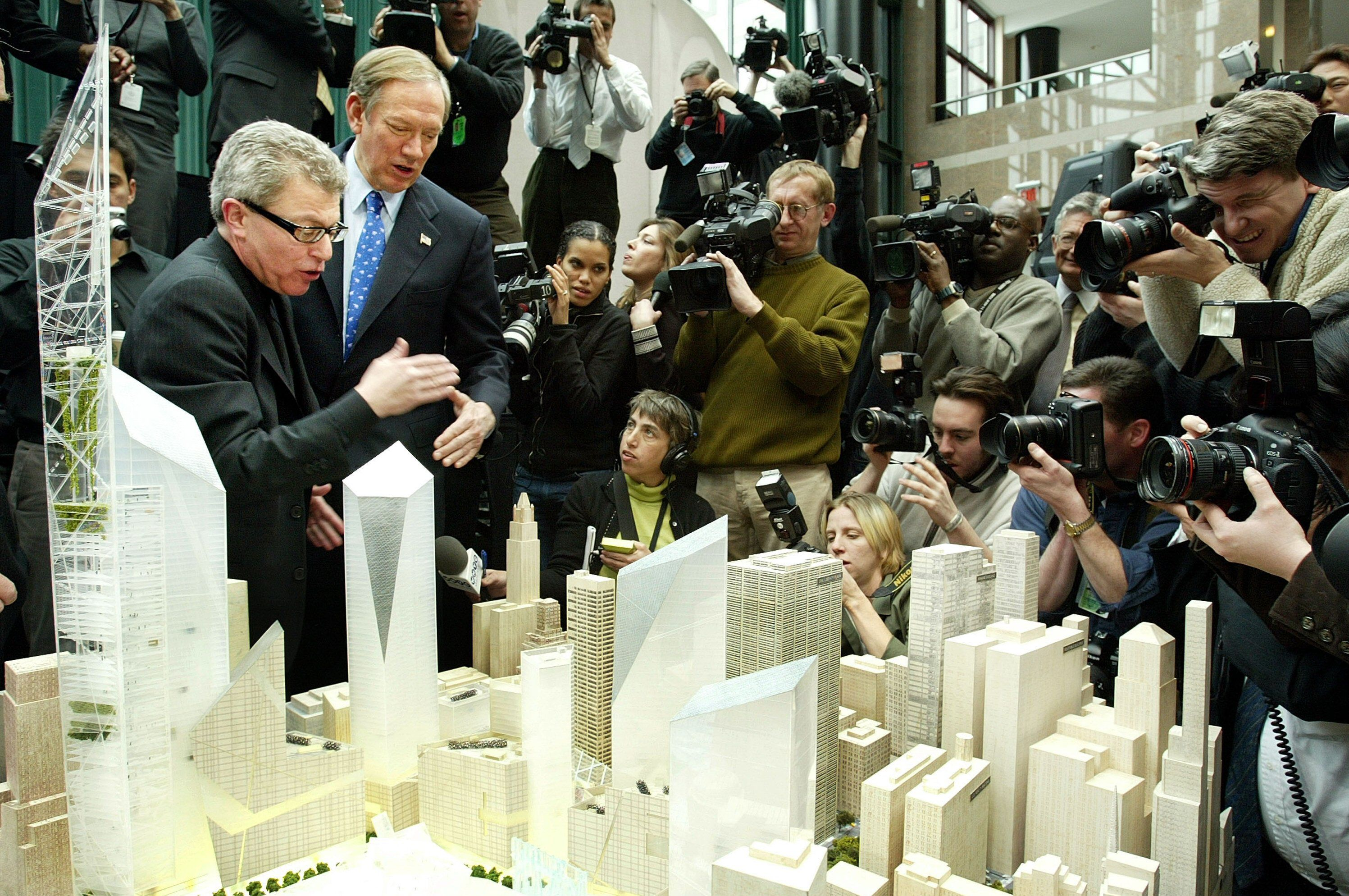 Architect Daniel Libeskind (L) presents his winning design for the World Trade Center site to New York Governor George Pataki (2nd-L) at a media conference