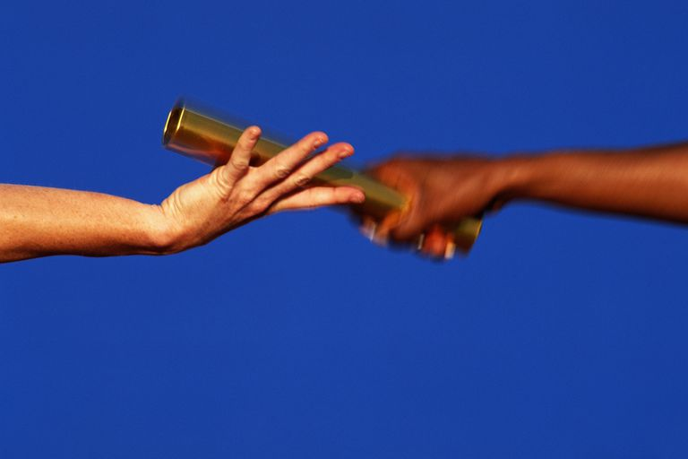 relay runners passing a baton - closeup of the hands