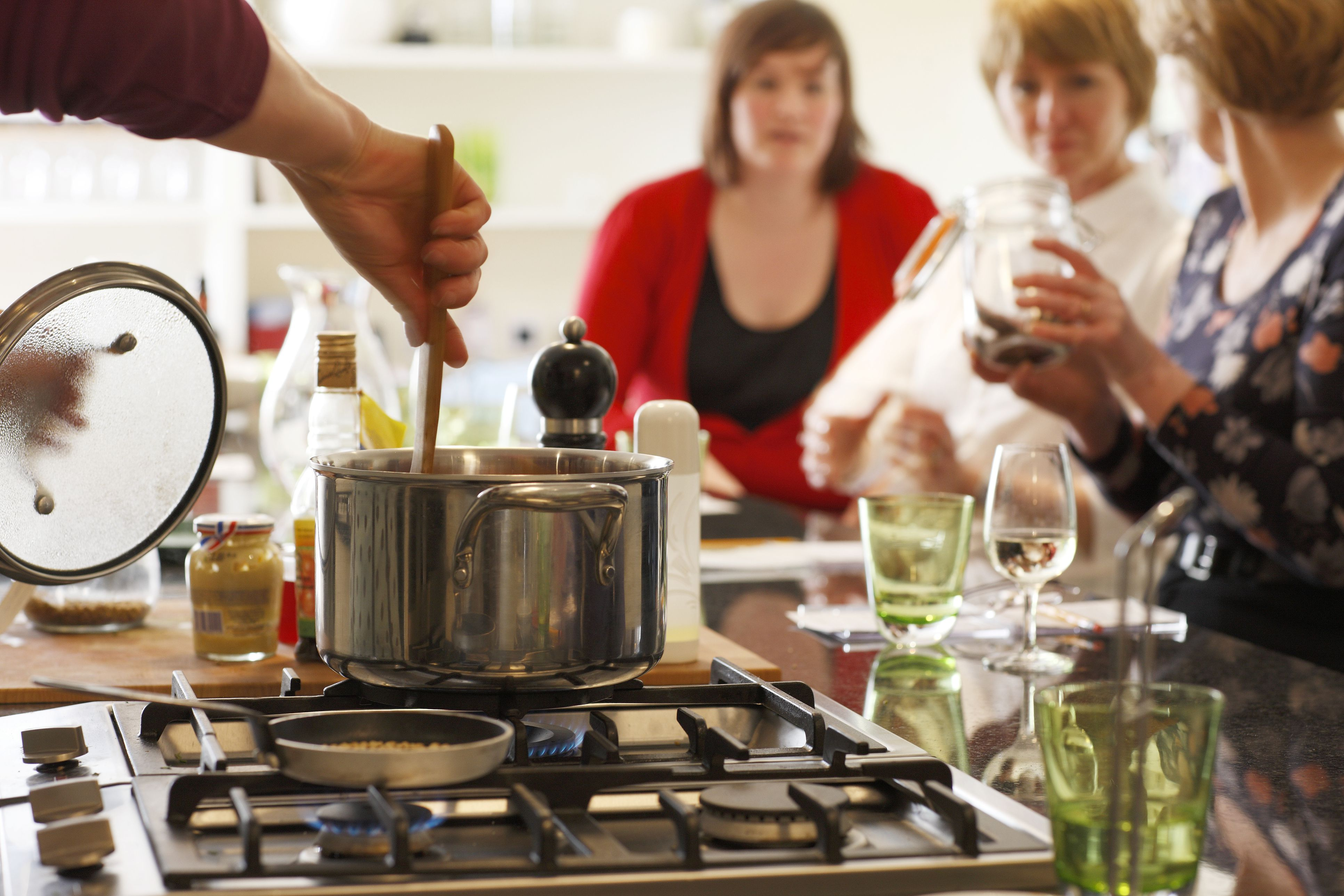 Stirring a pot on a stove in a kitchen island with guests in the background.