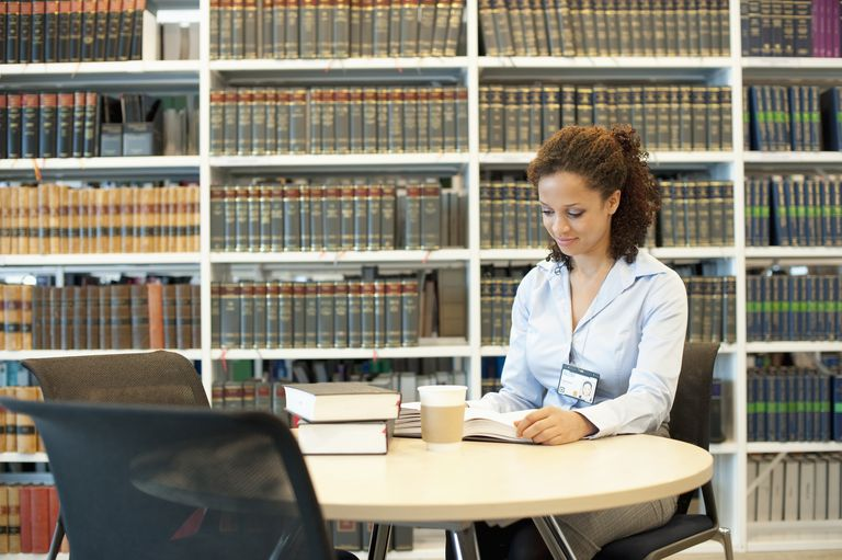 Mixed race businesswoman reading at desk in law library
