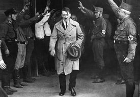 Adolf Hitler walking past a line of soldiers, black and white photograph.
